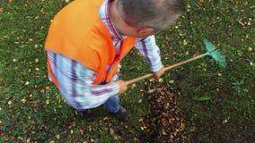 Lavoratore con il rastrello in un parco
