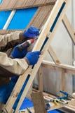 Lavoratore con il trapano elettrico che installa le mattonelle marroni del metallo del tetto sulla casa di legno Immagini Stock Libere da Diritti