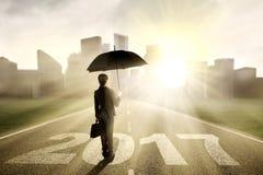 Lavoratore con l'ombrello e 2017 alla via Fotografie Stock Libere da Diritti