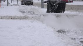 Lavoratore con la neve pulita del ventilatore di neve dal sentiero per pedoni sulla via nevosa all'inverno 4K video d archivio