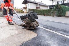 Lavoratore con la piastra vibrante - impianti d'asfaltatura Fotografie Stock