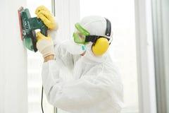 Lavoratore con la sabbiatrice al materiale da otturazione della parete Immagini Stock Libere da Diritti