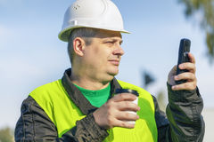 Lavoratore con la tazza di caffè ed il telefono cellulare Immagini Stock