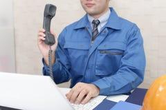 Lavoratore con un microtelefono fotografia stock