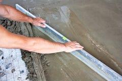 Lavoratore concreto dell'intonacatore sul lavoro del pavimento Immagine Stock