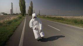 Lavoratore contaminato dell'ecologo nel vestito del hazmat che assicura e che cade giù sul modo dell'azionamento vicino alla raff stock footage
