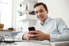 Lavoratore contentissimo che scrive sul suo telefono Immagine Stock Libera da Diritti