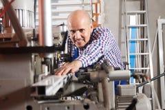 Lavoratore debonair professionista che lavora duramente su una macchina nel negozio del PVC immagine stock libera da diritti