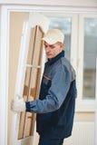 Lavoratore del carpentiere all'installazione della porta fotografia stock libera da diritti