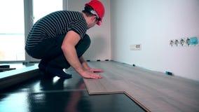 Lavoratore del carpentiere che installa pavimentazione laminata nella stanza stock footage