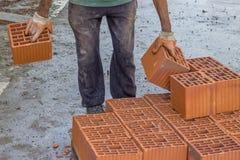 Lavoratore del costruttore che porta il blocchetto vuoto dell'argilla immagini stock