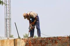 Lavoratore del costruttore con l'attrezzatura pneumatica del perforatore del martello pneumatico che fa foro in parete al cantier Fotografie Stock Libere da Diritti