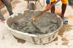 Lavoratore del costruttore durante per mezzo della zappa per mescolare cemento Fotografie Stock Libere da Diritti