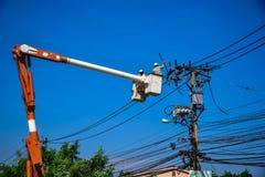 Lavoratore del gruppo che ripara lavoro sul palo di potere elettrico della posta Immagini Stock