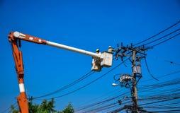 Lavoratore del gruppo che ripara lavoro sul palo di potere elettrico della posta Immagini Stock Libere da Diritti