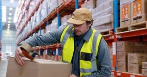 Lavoratore del magazzino che esamina i pacchetti archivi video