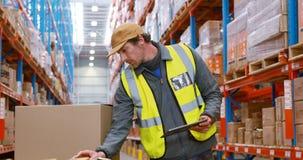 Lavoratore del magazzino che esamina i pacchetti video d archivio