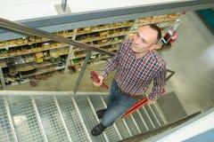 Lavoratore del magazzino che va su scale fotografie stock libere da diritti