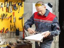 Lavoratore del meccanico che studia le sue istruzioni Immagini Stock