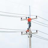 Lavoratore del riparatore del guardalinee dell'elettricista sul lavoro rampicante Fotografia Stock
