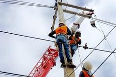 Lavoratore del riparatore del guardalinee dell'elettricista sul lavoro rampicante sul palo di potere elettrico della posta Immagini Stock Libere da Diritti