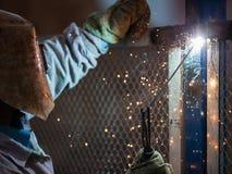 Lavoratore del saldatore dell'arco nella costruzione del metallo di saldatura della maschera protettiva Fotografia Stock