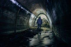 Lavoratore del tunnel della fogna in serie protettiva chimica in tunnel impregnato di gas sotterraneo della fogna immagini stock libere da diritti