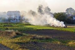 Lavoratore dell'agricoltore che fa un fuoco con fumo tossico delle foglie asciutte Immagine Stock Libera da Diritti