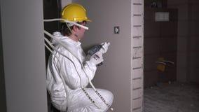 Lavoratore dell'elettricista all'installazione dell'incavo dello sbocco di parete dell'interruttore della luce e del cavo video d archivio