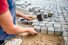 Lavoratore dell'industria che installa i blocchi di pietra sui lavori di costruzione della pavimentazione, della via o del marcia Fotografia Stock Libera da Diritti
