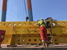 Lavoratore dell'industria con gli stivali di sicurezza e casco nell'azione Cielo blu profondo e costruzione gialla del ferro immagini stock libere da diritti
