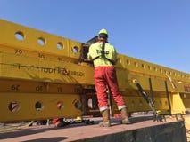 Lavoratore dell'industria con gli stivali di sicurezza e casco nell'azione Cielo blu profondo e costruzione gialla del ferro immagine stock