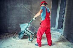 Lavoratore dell'industria, ingegnere sul cantiere, spingente una carriola fotografia stock