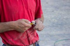 Lavoratore della costruzione che affila una matita con un coltello fotografie stock