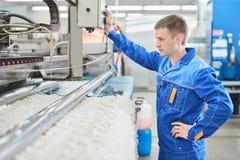 Lavoratore della lavanderia nel corso del lavorare alla macchina automatica per il lavaggio del tappeto Fotografie Stock Libere da Diritti