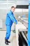 Lavoratore della lavanderia nel corso del lavorare alla macchina automatica per l'essiccamento dei tappeti Fotografie Stock