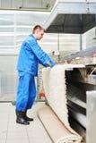 Lavoratore della lavanderia nel corso del lavorare alla macchina automatica per l'essiccamento dei tappeti Fotografia Stock Libera da Diritti