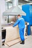 Lavoratore della lavanderia nel corso del lavorare alla macchina automatica per l'essiccamento dei tappeti Fotografia Stock