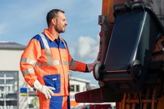 Lavoratore della raccolta dei rifiuti che mette recipiente nel camion residuo fotografia stock libera da diritti