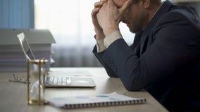 Lavoratore della società che si siede alla scrivania, tempie di lucidatura, stanchezza, lavoro straordinario video d archivio