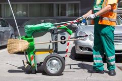 Lavoratore della società di pulizia in uniforme di verde con il bidone della spazzatura Fotografia Stock