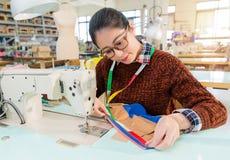 Lavoratore di cucito sorridente dell'abbigliamento femminile del professionista Immagine Stock