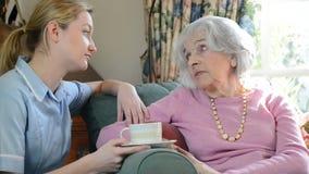 Lavoratore di cura che parla con donna senior depressa a casa archivi video