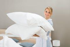 Lavoratore di governo della casa con i cuscini Fotografia Stock Libera da Diritti
