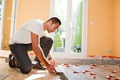 Lavoratore di industria dell'edilizia con gli strumenti che rinnova casa con le piastrelle per pavimento in un cantiere fotografie stock libere da diritti