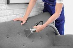 Lavoratore di lavaggio a secco che rimuove sporcizia dal sofà fotografie stock libere da diritti