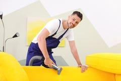 Lavoratore di lavaggio a secco che rimuove sporcizia dal sofà immagine stock libera da diritti