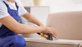 Lavoratore di lavaggio a secco che rimuove sporcizia dal sofà all'interno immagini stock