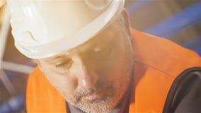 Lavoratore di mezza età del primo piano del movimento lento in casco bianco archivi video
