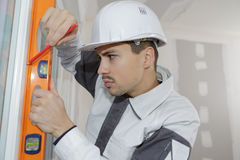 Lavoratore di Onstruction che controlla a livello sulla parete all'interno Immagine Stock